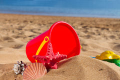 Bucket with seshells in sand on sea shore Royalty Free Stock Photos