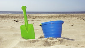 Bucket and shovel on the beach. Child's bucket and shovel on the beach royalty free stock photography