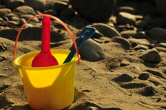 Bucket and shovel on the beach. Classic shot of fun in the sand with bucket and shovel stock photo