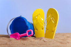Bucket, shovel and flipflops on the beach Stock Photography