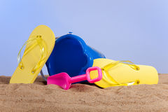 Bucket, shovel and flipflops on the beach Royalty Free Stock Images