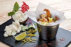 A bucket of shrimp in Asian style with rice on coconut milk stock image