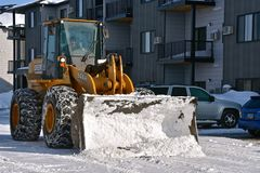 Bucket of snow dumped into a pile. FARGO, NORTH DAKOTA, March 11, 2019: A huge 4-wheel drive tractor644H with a massive bucket for snow removal tractor is a stock photography