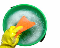 Bucket of Soapy Water. Close-up of a bucketful of soapy water with a rubber-gloved hand holding a cleaning sponge. Isolated over pure white royalty free stock photo