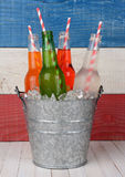 Bucket of Soda with Drinking Straws. Closeup of a bucket of soda bottles with drinking straws against a red, white and blue background for a 4th of July picnic Royalty Free Stock Images