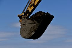 Bucket of soil in an excavating machine. The huge bucket of an excavating machine is filled with black soil stock photography