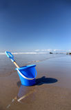 Bucket and spade. Blue bucket and spade rests on tranquil beach stock photo