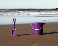 Bucket and spade on beach. Purple bucket and spade on beach stock photography