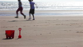 Bucket and spade with children skipping stock video footage