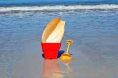 Bucket and spade with large cone shell on the beac Stock Image