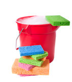 Bucket and Sponges. A red plastic bucket on a white background with several brightly colored sponges.  Cleaning theme Royalty Free Stock Photo