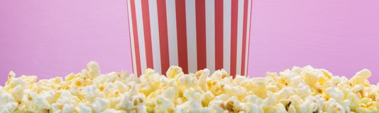 The bucket stands on a scattered popcorn, on a pink background stock photography