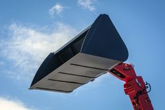 Bucket of a telescopic loader in black, against the sky stock photo