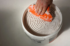 Bucket of tile adhesive. Male hand scraping adhesive out of bucket with spreader royalty free stock images