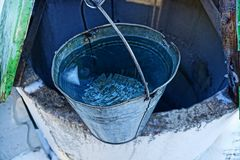 A bucket of water on the edge of a well Stock Image