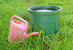 A bucket of water and watering can on the grass. Royalty Free Stock Images