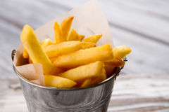Bucket with yellow fries. French fries and paper. Product that harms your health. Eat less junk food Royalty Free Stock Images
