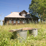 Buckets on the background of a village house royalty free stock photography