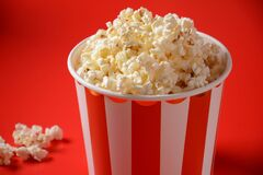 Buckets with delicious popcorn on red background.