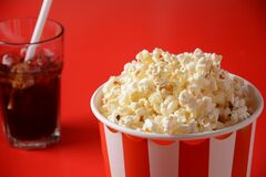 Buckets with delicious popcorn on red background. Spilled popcorn