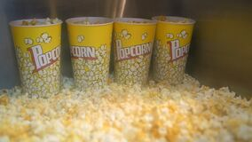 Buckets and fresh popcorn pile on display in fastfood cafe