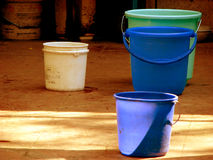 Buckets n' Colors. Colorful buckets look beautiful on a textured floor Royalty Free Stock Photos