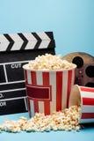 buckets of popcorn, clapperboard and film bobbin on blue, cinema concept.