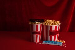 Buckets with popcorn near medical mask with stay at home lettering and sunglasses on red surface with velour