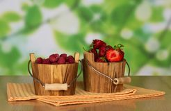 Buckets with raspberry and strawberry. Bucket with raspberry, a bucket with strawberry, and napkins on a table Stock Image