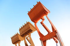 The buckets/shovels of heavy construction machine raised against Royalty Free Stock Images