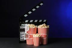 Buckets with tasty popcorn and movie clapper on dark background