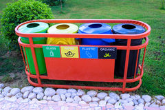 Buckets for waste sorting. Four recycle bins with garbage icons standing in a row outside. Waste bins in one for recycle sorting Stock Photography