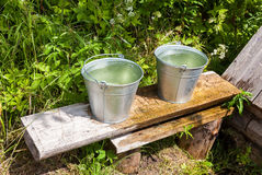 Buckets of water standing on a bench at the water well Royalty Free Stock Photography