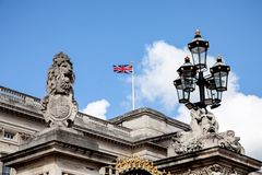 Buckingham Palace with british flag, lion with king crown, royal family. LONDON, UK - May 4, 2019. Buckingham Palace with british flag, lion with king crown stock photos