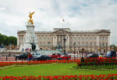 Buckingham Palace and gardens. A view of Buckingham Palace including a garden full of red flowers Royalty Free Stock Photos