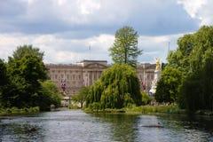 Buckingham Palace mit Teich und Bäume in der Front Hochgezogene Flagge London, Gro?britannien lizenzfreie stockfotografie