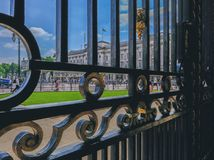 Buckingham Palace viewed through the ornate South African Gates. London, UK - June 8, 2018: Front view of Buckingham Palace from behind the black ornate South Stock Photography