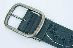 Buckle on leather belt. A macro image of the buckle of a decorated leather belt set against a plain bright background Stock Photo