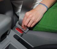 Buckle up. Young driver fastening seat belt Stock Photos