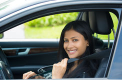 Buckle up. Closeup portrait young smiling, happy, attractive woman pulling on seatbelt inside black car. Driving safety, buckle up to prevent traffic death from Stock Images
