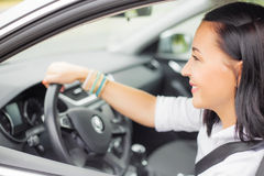 Buckled up woman driving with hand on steering wheel Royalty Free Stock Photos