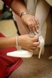 Buckling help. Maid of honor buckling bride's shoe Stock Photo