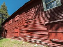 Long red wall, old hotel. Buckling siding, long wall on an old mountain hotel royalty free stock photo
