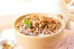 Buckweat with milk. Buckweat porridge with milk and mint on white napkin, close up, horizontal. Natural organic vegetarian food (breakfast royalty free stock image