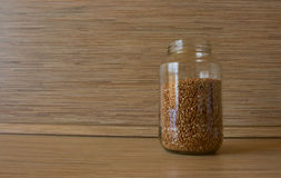 Buckwheat in a bank. On the table Royalty Free Stock Image