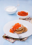Buckwheat blini with red caviar and sour cream Stock Photos