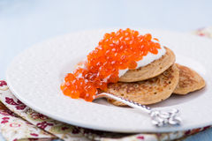 Buckwheat blini with red caviar and sour cream. On white plate, selective focus royalty free stock photography