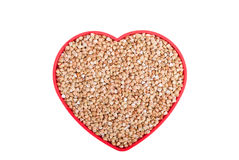 Buckwheat in a bowl in the shape of heart. Royalty Free Stock Images