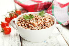 Buckwheat in bowl on white wooden background Stock Photo
