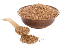 Buckwheat in bowl with wooden spoon on white. Stock Photos
